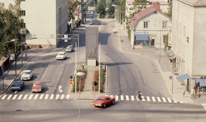 Kesäinen katunäkymä Kymen Lukolta v. 1970.  Kuvassa Vapauden patsas  Salpausselänkadun ja Kauppalankadun risteyksessä. Kuvassa henkilöautoja ja Salpaussselänkadun rakennuksia.