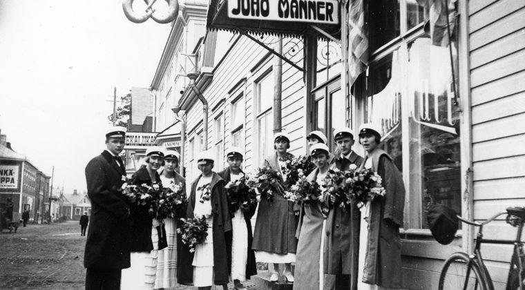 Kouvolan Suomalaisen Yhteiskoulun ylioppilaat Juho Mannerin kahvilan edustalla Kauppalankadulla keväällä 1924. Kirjoitukset läpäisi 8 tyttöä ja 3 poikaa. Yksi poika puuttuu kuvasta.