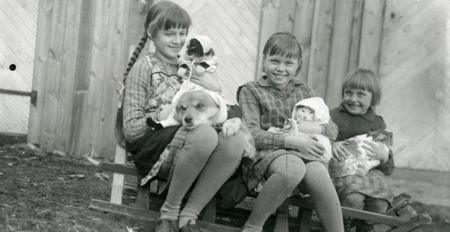 Kuukauden kuva elokuu 2019: Naapuruston tyttöjä lemmikkeineen Forsströmin ulkorakennuksen edessä 1930-luvun alussa Kuusankosken Kyöperilässä. Kuvassa vasemmalta: Paula Forsström (myöh. Sipilä), Toini Tammelin ja Hilkka Tammelin.