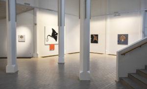 Osmo Rauhan näyttely Järjestyksen kuvat Kouvolan taidemuseo Poikilossa 12.1.2020 asti. Taidemuseon seinällä taidetoksia, jotka kuvaavat rauskuja.
