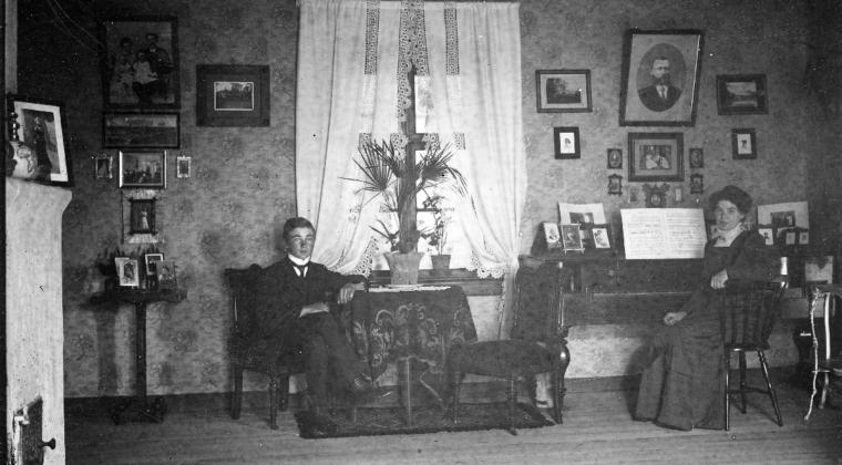 Puutarhuri Nilssonin pianosali Sippolassa v. 1912. Kuvassa nuori mies istuu pöydän ääressä , jossa on kukka pöydällä. Nainen istuu pianon ääressä. Seinällä on tauluja. Huoneessa on ikkuna, jossa valkoiset verhot.