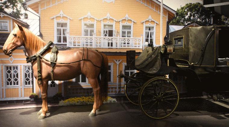 Mustilan kartanon kuomuvaunut, joita vetää ruskea hevonen. Taustalla keltainen kartanorakennus.