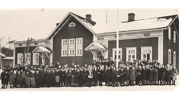 Kuusankosken lukio 100 vuotta. Kuusankosken Yhteiskoulu aloitti toimintansa syksyllä 1920 Kuusankosken seuratalossa, josta se muutti Vanhaan kasarmiin marraskuussa 1925 toimien siinä vuoteen 1941 saakka. Kuvassa Yhteiskoulun oppilaita Vanhan kasarmin sisäpihan puolella. Rakennuksen katon keskiosassa oli harjakatto, kun taas Marskinkadun puolella keskiosassa oli mansardikatto.
