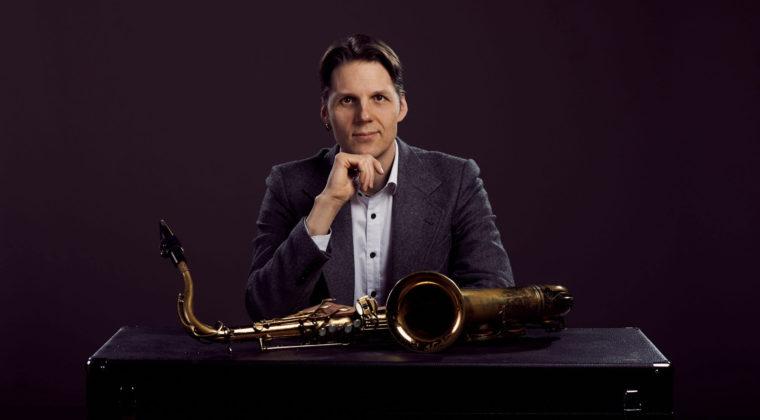 Saksofonisti Masa Orpana istuu pöydän ääressä saksofoni edessään.