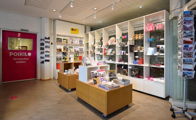 Poikilo-museoiden museokauppa. Myytäviä tuotteita hyllyillä, kirjoja, lahjatavaroita ja etualalla telineiden päällä koruja, kalentereita. Takana punainen ovi taidemuseoon.