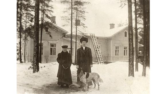 """Talvinen näkymä Voikkaan tehtaan isännöitsijän asunnon Kuukerpallin edustalta 1910-luvun alussa. Oikealla Hilma Nieminen, joka oli tuolloin Norrmanilla sisäkkönä, vierellään rouva Mari Norrman sekä isännöitsijän """"Heiju""""-setteri."""
