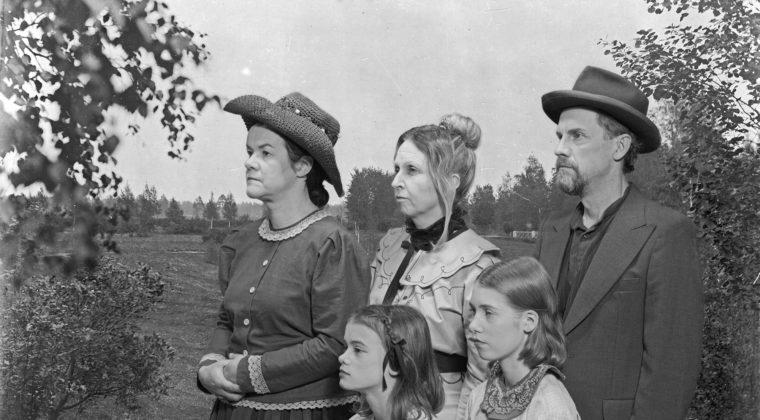 Ryhmäkuva, jossa kaksi naista ja mies sekä kaksi tyttöä puutarhamaiseman edessä seisomassa entisajan vaatteissa.
