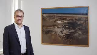Kehitysjohtaja Petteri Portaankorva Kouvolan kaupungintalossa haastateltavana työhuoneessan olevasta Esko Tirrosen taideteoksesta Merimaisema.