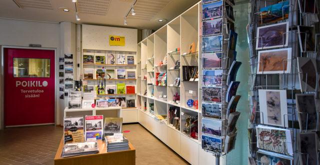 Museokauppa. Hyllyillä julkaisuja ja myytäviä tuotteita, kkortteja, tarjottimia, mukeja jne.