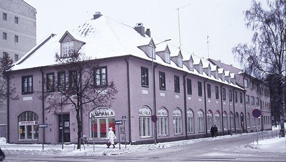 Talvinen näkymä vanhasta Kirjapainotalosta 1980-luvun puolivälissä. Rakennuksessa toimivat tuolloin kangaskauppa Hal-Pala, Kuva-Sävilä ja Eetun Halpahalli. Kuvaaja Heikki Rautio.