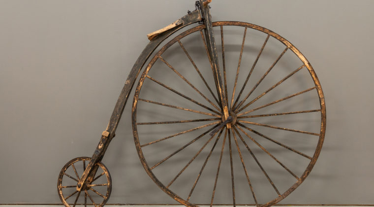 Puinen korkea polkupyörä, jonka etupyörä on suuri ja takapyörä pieni. Satula on suuren etupyörän päällä ja polkimet ovat etupyörän navassa.