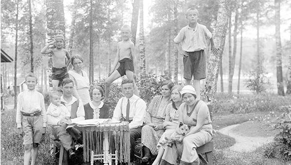 Valokuvaaja Aarne Aarnion perhe viettämässä vuonna 1932 kesäpäivää Voikkaan Yrjönojan virkamiestalon puutarhassa. Perhe istuu pöydän ääressä ja lapsia seisomassa takana. Seurueessa mukana myös koira.