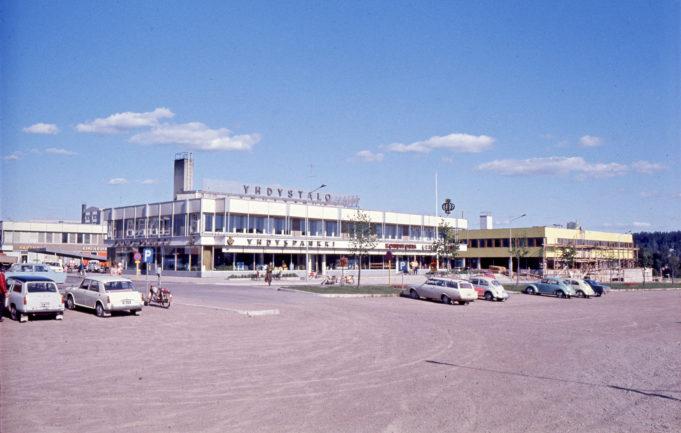 Kuusankosken keskustaa kesällä 1969. Etualalla on vuonna 1965 valmistunut Yhdystalo ja oikealle on valmistumassa Ostoskeskuksen liikerakennus. Kuvaaja tuntematon.