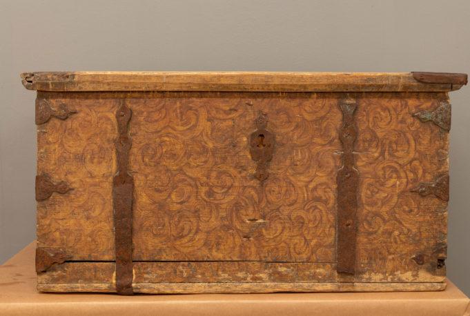 Puinen tasakantinen arkku, joka on koristeltu puun syykuvioita jäljittelevällä ruskealla maalauksella.